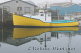 Yellow lobster boat in fog at Fishermans Cove Eastern Passage Halifax Nova Scotia