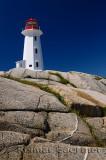 Peggys Cove lighthouse on smooth granite rocks against a blue sky Nova Scotia