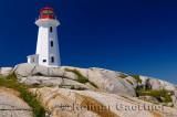 Peggys Cove lighthouse on top of smooth granite rocks against a blue sky Nova Scotia