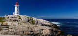 Peggys Cove Nova Scotia lighthouse on worn granite rocks with accordian player tourists and surf