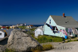 Rural fishing village houses with laundry and the lighthouse at Peggys Cove Nova Scotia