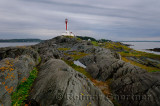Cape Forchu lighthouse peninsula with wet rocks and grass Yarmouth Harbour Nova Scotia