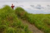 Girl tourist on Port Maitland beach sand dunes with grass Nova Scotia