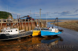 Boats moored at the Alma wharf at sundown low tide on the Bay of Fundy New Brunswick