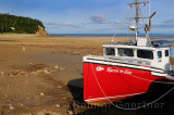 Young girl walking on Ocean floor next to an achored boat on the Bay of Fundy Alma New Brunswick
