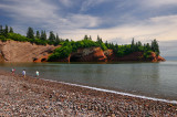 Children playing on pebble beach at sea caves of St Martins New Brunswick at Bay of Fundy high tide