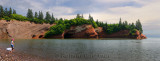 Panorama of children playing on pebble beach at sea caves of St Martins New Brunswick