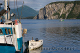 Fishing boat leaving East Arm Bonne Bay at Norris Point at the end of the day with Shag Cliff