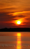 Red ball sunset and reflection from Rocky Harbour Newfoundland with Lobster Cove lighthouse