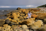 Traveler pointing at rust colored boulders on the shore of Martins Point Newfoundland