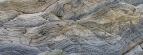 Panorama of abstract pattern of wavy sedimentary layers of stone at Bay of Fundy Cape Enrage
