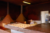Moroccan woman baking bread in a wood burning oven early in the morning at El Jedida