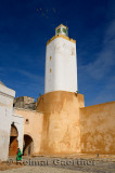 Grand Mosque minaret with old lady in green in Old Portuguese city of El Jadida Morocco