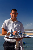 Friendly server offering mint tea for lunch at seaside resort at Oualidia Morocco