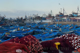 Blue fishing boats and red nets at early dawn in the marine port of Essaouira Morocco