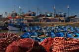 Blue fishing boats and red nets in the morning at the marine port of Essaouira Morocco
