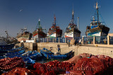 Red nets and fishermen getting ready to sail in the morning at the marine port of Essaouira Morocco