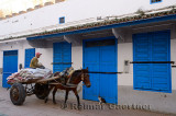 Moroccan man on a pony drawn cart in Essaouira Medina with blue doors and cat in early morning