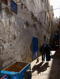 Mother and daughter walking down a narrow Essaouira Medina street in morning light