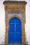 Fresh painted blue door with stonework and tiles in Essaouira Medina on white building