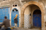 Passersby and blue doors in Essaouira Medina with ornate stonework and Zellige tilework