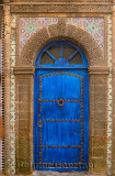 Blue door in Essaouira Medina with ornate stonework and Zellige tilework