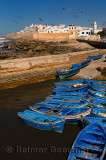Blue fishing boats and the sea bastion ramparts of Essaouira Morocco