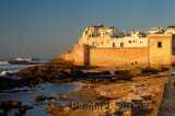 Golden glowing sea bastion ramparts of Essaouira Morocco at sunset