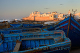 Blue fishing boats and Atlantic Ocean surf with the ramparts of Essaouira Morocco at sunset