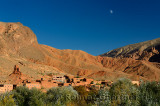 Moon in blue sky over red soil and rock formations in Dades Gorge Morocco