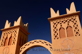 Traditional Berber pise towers made of red adobe and blue sky at resort in Dades Valley