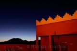 Orange adobe crenellations on rooftop of resort with indigo sunset in Tinerhir Morocco