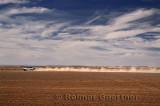 Dust trail of 4x4 car speeding from Erfoud to the Erg Chebbi desert Morocco