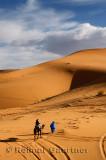 Tuareg Berber man leading a tourist on camel through the Erg Chebbi desert in Morocco