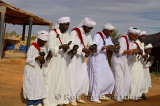 Group of Gnawa musicians in white turbans and jellabas dancing and playing krakebs in Khemliya Morocco
