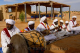 Gnawa musicians singing and playing while sitting in the desert street of Khemliya Morocco