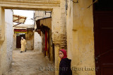 Moslem man in jellaba and white cap with young girl in yellow Fes el Bali Medina Morocco