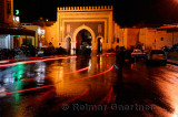 Car taillight reflections on wet Place Boujeloud with Blue Gate Morocco at night