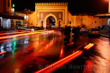 Car taillights reflected on wet Place Boujeloud with Blue Gate Morocco at night
