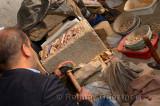 Craftsman freehand chiseling glazed terra cotta pieces for Zellige tilework Fes Morocco