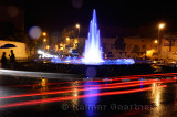 Couple under umbrella at night with wet traffic circle and blue fountain in Medina of Fes Morocco