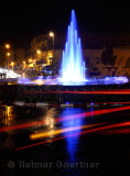 Car taillight reflections on wet Fes el Bali Medina traffic circle with blue fountain at night Morocco