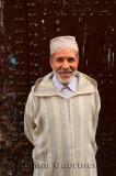 Smiling Moroccan man in djellaba and cap against an old door in el Bali Medina of Fes Morocco