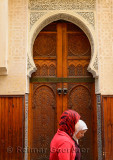 Two women in red hijab passing ornate wooden doors of a Mosque in Fes Medina Morocco