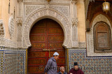 Men at the ornate door of Sidi Ahmed Tijani Mosque with intricate stone carving and tilework in Fes Morocco