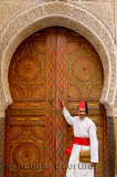 Man in white robe and red cap and sash at door of Mosque with intricate stone carving and paint in Fes Morocco