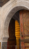 Open door of Mosque with intricate stone carving Zellige and paint in Fes Medina Morocco