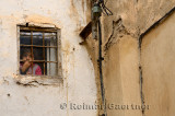 Pensive young girl staring out a small window in the el Bali Medina of Fes Morocco