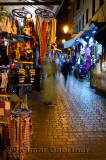 Blurred shoppers and shops on a rainy night in Fes el Bali Medina Morocco