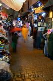 Blurred pedestrians shopping on a rainy night in Fes el Bali Medina Morocco